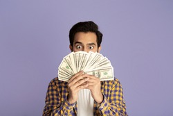 Winning lottery. Excited Indian guy with heap of money on violet background