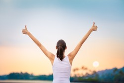 Winning, success and life goals concept. Young woman with arms in the air giving thumbs up.