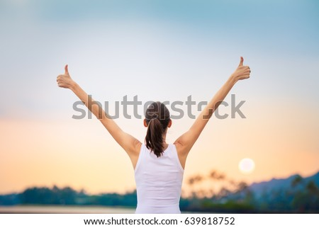 Winning, success , and life goals concept. Young woman with arms in the air giving thumbs up.