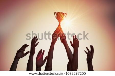 Winning team is holding trophy in hands. Silhouettes of many hands in sunset.