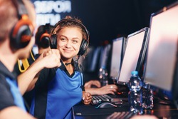Winning. Two young happy professional cyber sport gamers giving fist bump and celebrating success while participating in eSports tournament