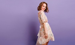 Winsome girl in romantic attire pretty smiling on purple background. Slim curly female model in white dress looking to camera with shy face expression.