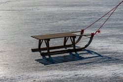 Winter activity for childhood, Low angle of wooden sled on hard and thick ice in the lake with rope,