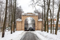 Winter alley with trees, brick arch and cast-iron gate - the entrance to a large city park