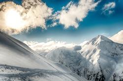 Winter Alpine snowpeak background with ountainous terrain and snow covered trees texture. Bansko, Bulgaria