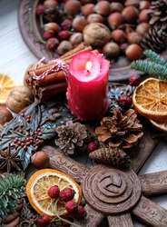Winter altar for Yule sabbath. pagan holiday. Red candle, wheel of the year, cinnamon, nuts, cones, dry orange slices. Witchcraft Esoteric Ritual for Christmas, Yule, Magical Winter Solstice