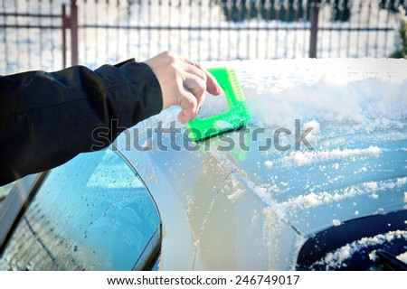 Winter and car. Person remove snow from car. Car covered with snow and ice.