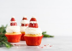 Winter and new year cupcakes in red paper cups with creamy frosting and strawberry santa clause on the top. Christmas dessert, new year cooking. Copy space. White background.