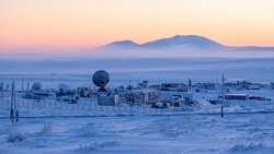 Winter Arctic industrial landscape. Large satellite dishes in the snow-covered tundra. Telecommunications in the Far North of Russia. Cold weather. Northern climate of Chukotka and polar Siberia.