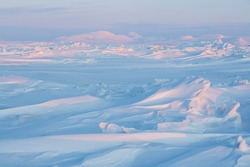 Winter arctic landscape. Cold frosty winter weather. Harsh polar climate. Ice hummocks on the frozen sea in the Arctic. View of snow and ice at sunset. Picturesque nature of the Arctic. Far North.