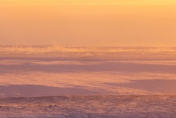 Winter arctic landscape. Morning aerial view of snowy tundra and frozen sea. Cold windy and frosty weather. Blowing snow. Beautiful golden light at sunrise. Chukotka, Polar Siberia, Far North Russia.