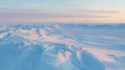 Winter arctic landscape. View of snow and ice at sunset. Ice hummocks on the frozen sea in the Arctic. Cold frosty winter weather. Harsh polar climate. Travel and hikes to the far north to the Arctic.