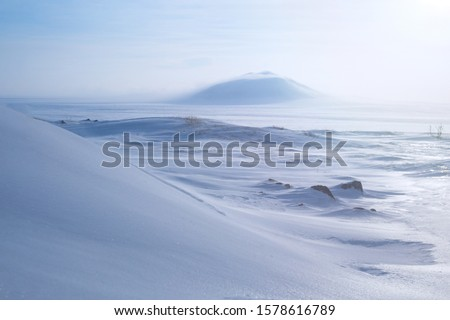 Photo of  Winter arctic landscape with snow covered tundra and hills. Very cold frosty weather in April in the far north of Russia. Location place: Chukotka, Siberia, Russian Far East. Polar region.