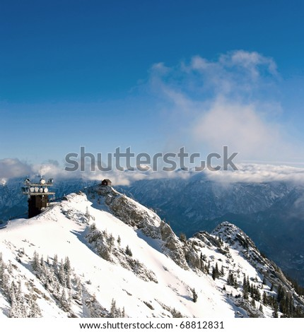 Winter Austrian Alps - telecommunication tower on top of snowy mountain with alpine range in the background