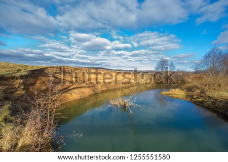 Winter, autumn landscape. The river with ice, trees without leaves, dark sky, withered grass. The earth is waiting for snow, snow drifts. #1255551580