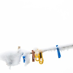 winter background: clothesline covered with snow, several colored clothespins, selective focus