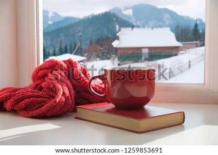 Winter background - cup with candy cane, woolen scarf and gloves on windowsill and winter scene outdoors. Still life with concept of spending winter time at cozy home with cold weather outdoors