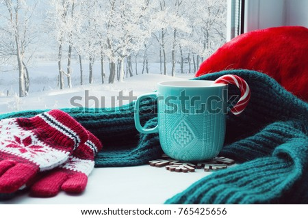Winter background. Cup with candy cane, woolen scarf and red gloves on windowsill and winter forest outside. Still life with concept of spending winter time at cozy home