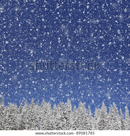 Winter background for design. Falling snow against the blue sky and trees