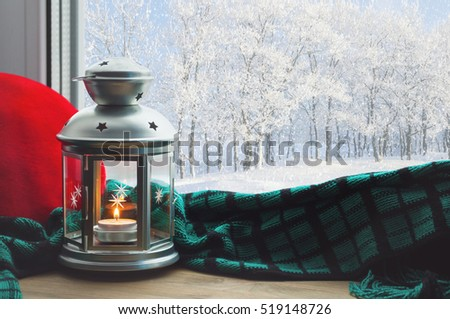 Winter background-lantern with burning candle on windowsill and winter forest outdoor.Winter still life with winter concept -winter background. Winter background evening in home and winter outside