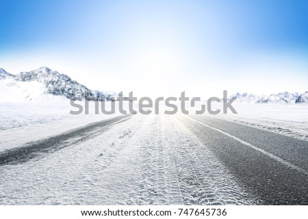 Winter Background of foreground of road covered with snow and ice. In the background, the arctic landscape of the mountains with the beautiful blue sky.