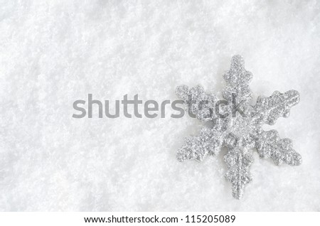 Winter background shot from above.  Glittery silver Christmas snowflake faces upwards on lower right, lying in fake snow.