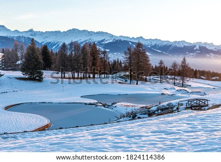 Winter background. Snow, icy water, trees and mountain in Crans Montana in Switzerland. Tranquil scene. Photo stock ©