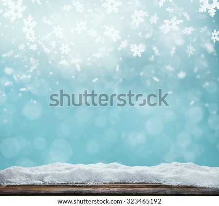 Shutterstock Winter background with pile of snow and blur abstract lights. Empty wooden planks on foreground. Copyspace for text