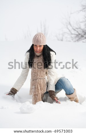 winter beautiful girl is grabbing a snow to make a snow ball. Winter fun concept