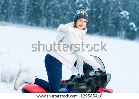 Winter, beautiful woman and a snowmobile, horizon format