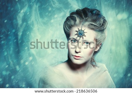 Winter beauty fantasy woman portrait. Beautiful glamour model girl with Christmas fashion makeup and hairstyle. Holiday style. Trendy exclusive jewelry. Snow queen. Grain added for best impression.