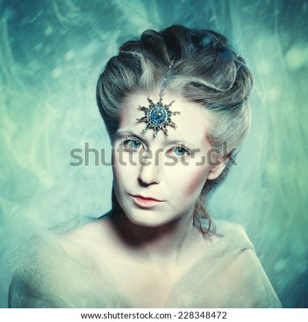 Winter beauty fantasy woman portrait. Beautiful glamour model girl with Christmas fashion makeup and hairstyle. Holiday style. Snow queen. Instagram retro effect. Grain added for best impression.