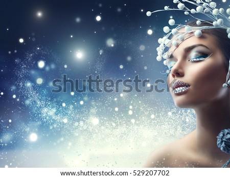 Winter Beauty Woman. Christmas Girl Makeup. Make-up. Beautiful young woman face closeup, winter snow eyelashes and eyeshadow, lips with diamonds.