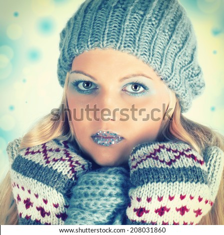 Winter Beauty Woman with hat, scarf and gloves. Christmas Makeup. Snow Queen High Fashion Portrait over Blue Snow Background. Eyeshadow and Crystals on the Lips.
