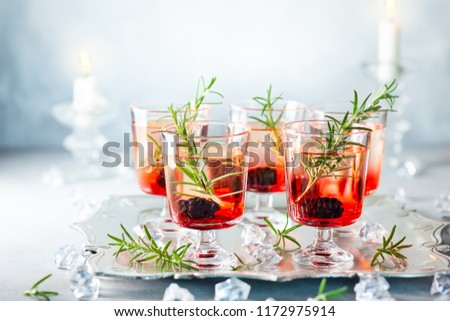 Winter berry cocktails made with blackberry liqueur and gin for Christmas or New Year. Served with fresh blackberry and rosemary on the silver tray.