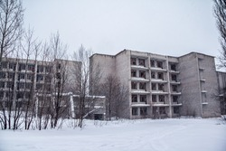 Winter, blizzard, snow, old ruined five-storey building, the concept of loneliness and despair
