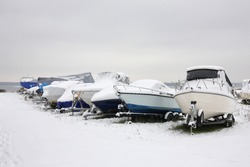 Winter boats parking - average boats on trailers in snow.