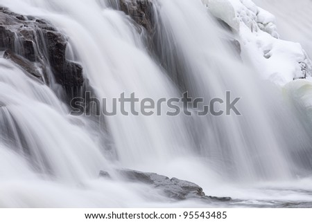 Winter, Bond Falls cascade captured with motion blur and framed by ice and snow, Michigan's Upper Peninsula, USA