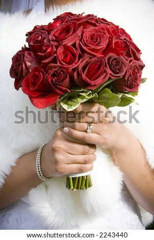 winter bride  in beautirul fur shawl holding bouquet of red roses