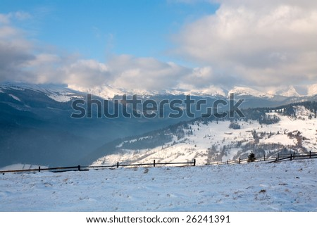 winter calm mountain landscape with rime and snow covered spruce trees.