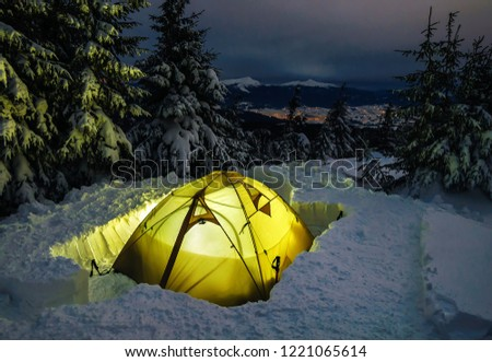 Winter camping, night, shining green tent on snow, clouds, forrest. Night shot, long exposure, sleeping on snow in the outdoors.
