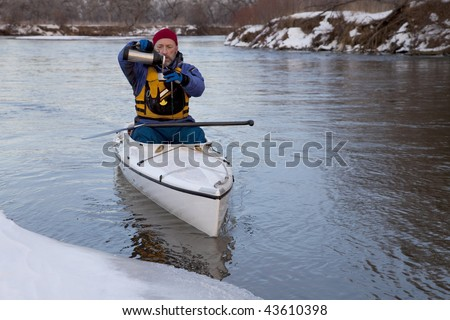 winter canoe paddling on icy river, taking a break for hot tea (South Platte River in eastern Colorado)
