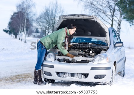 Winter car breakdown - woman try to repair motor