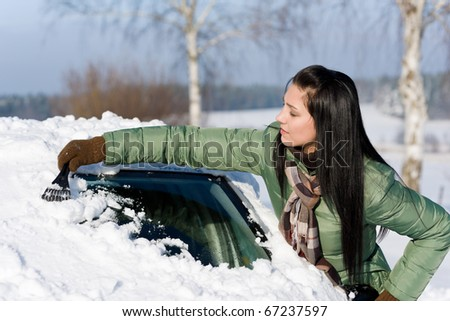 Winter car - woman remove snow from windshield with ice scraper