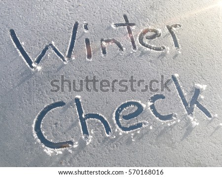 Winter Check drawn on a car windshield covered with fresh snow and ice