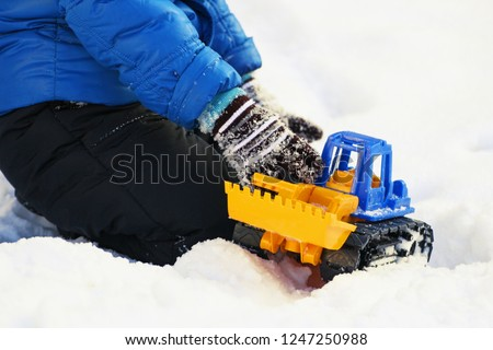 Winter. Child playing in the snow. Image of a child sitting on white snow and playing with a toy excavator.