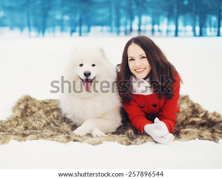 Winter, christmas and people concept - happy woman having fun with white Samoyed dog outdoors on the snow in winter day