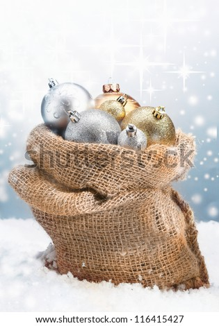 Winter Christmas baubles piled high in a rustic burlap bag nestled in fresh snow with a backdrop of twinkling stars on falling snowflakes - stock photo