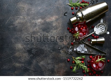 Winter christmas cocktail with cranberry and rosemary in a glasses on a dark slate, stone or concrete background. Top view with copy space.