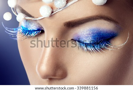 Winter Christmas eyes make up with glitter blue eyeshadows and false eyelashes. Party art model Woman makeup. Creative Girl Holiday Make-up. Snow Queen High Fashion Portrait over Blue Background